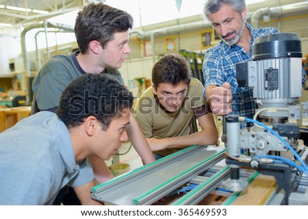 Apprentices learning to use machine