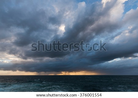 Approaching storm cloud with rain over the sea during sunrise - stock photo