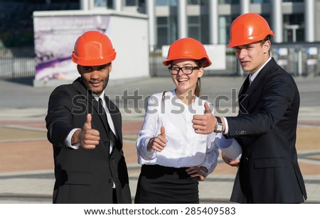Approval of the business plan of the new building. Three confident business architect in protective helmet standing on the site and view the object holding blueprints in hand