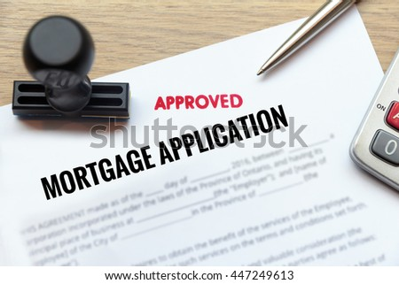 Approved mortgage application form lay down on wooden desk with rubber stamp and calculator.