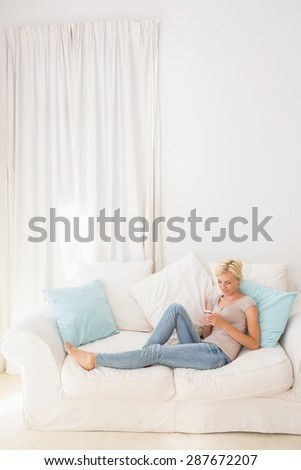 appy blonde woman using her mobile on the sofa at home in the living room