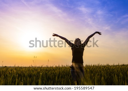 appy young girl in a field, with a feeling of freedom.