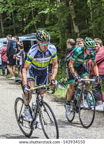 APREMONT,FRANCE-JULY 13 : Two cyclists (Stuart O'Grady and  Davide Malacarne ) climbing the road to mountain pass Granier during the stage 12 of Le Tour de France in Apremont on 13 July 2012. - stock photo