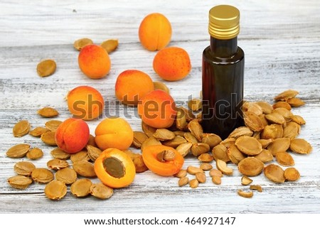 Apricot oil from  apricot kernels in a brown bottle , apricot seeds around and  fresh apricots on wooden table