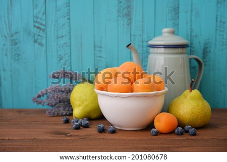 Apricots in bowl with fresh pear and blueberry on wooden background