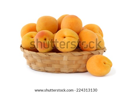 Apricots in wicker basket isolated on white background - stock photo