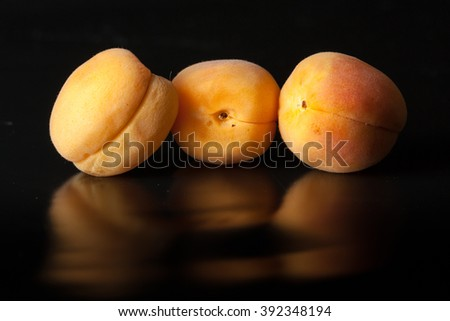 Apricots on black reflective background - stock photo