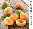 Apricots with leaves on the old wooden table. - stock photo
