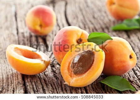 Apricots with leaves on the old wooden table.