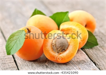 Apricots with leaves on wooden texture
