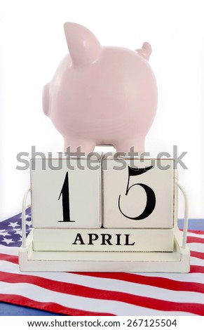 April 15 calendar for USA Tax Day with piggy bank on stars and stripes flag against a white background. - stock photo