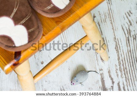 April Fool's Day concept with mouse and feet frightened woman - stock photo