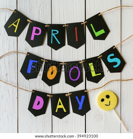 April fools day black banner colorful lettering on white barn wood rustic planks background. Holiday greeting postcard. - stock photo