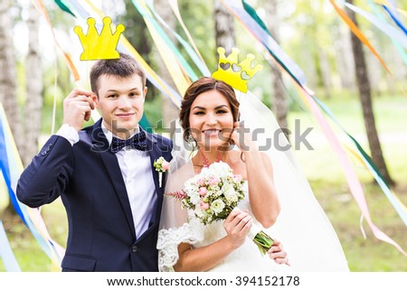 April Fools' Day. Wedding couple posing with crown, mask. - stock photo