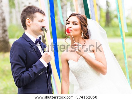 April Fools' Day. Wedding couple posing with mask. - stock photo