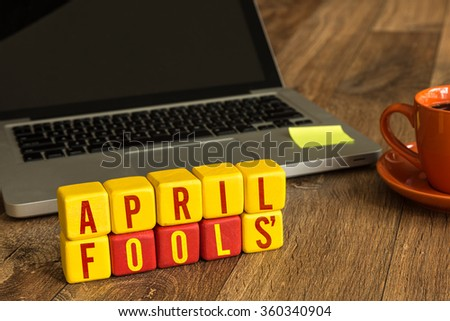 April Fools' written on a wooden cube in a office desk - stock photo