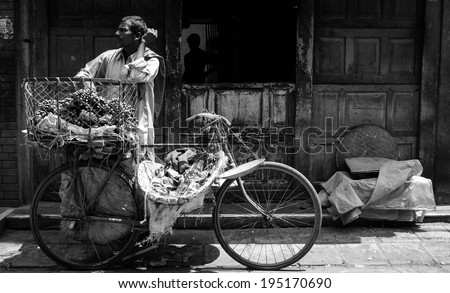 April 16, 2010 Kathmandu, Nepal. A fruit Merchant with his bicycle basket full of fruit waiting for a customer to buy. Black and White photo makes it more dramatic. - stock photo