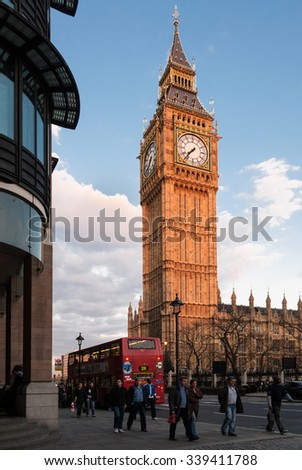 April 10, 2007 - London, UK: Unidentified people and a red double decker bus in front of Big Ben at sunset. The Houses of Parliament's iconic clock tower is one of London's most famous landmarks. - stock photo
