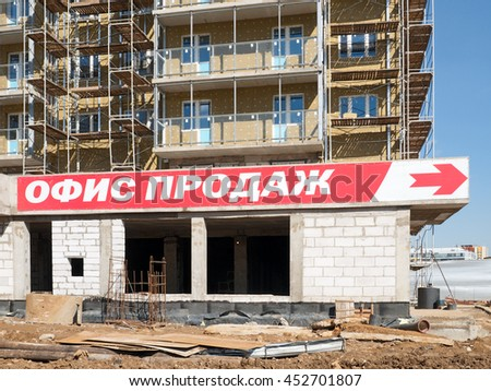 "April 2014, Moscow, Russia. The construction of a house. On the facade design banner-sign ""Sales Office"""