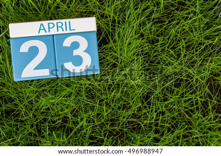April 23rd. Day 23 of month, calendar on football green grass background. Spring time, empty space for text