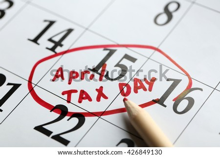 April tax day written and circled in a calender on date of 15th, close up - stock photo