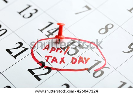 April tax day written and pinned in a calender on date of 15th, close up - stock photo