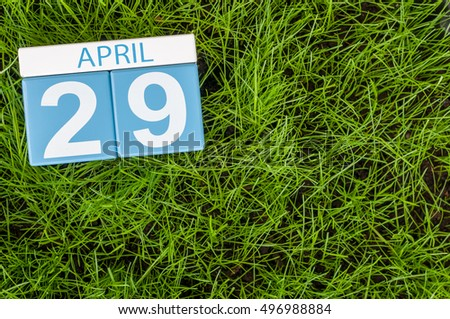 April 29th. Day 29 of month, calendar on football green grass background. Spring time, empty space for text