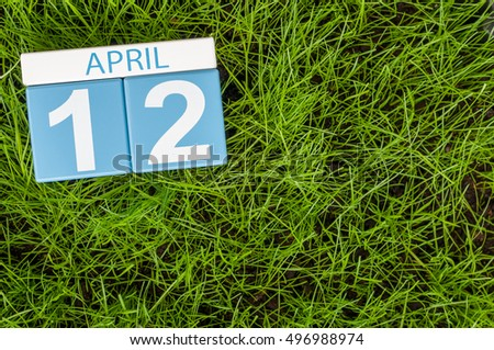 April 12th. Day 12 of month, wooden color calendar on football green grass background. Spring time, empty space for text