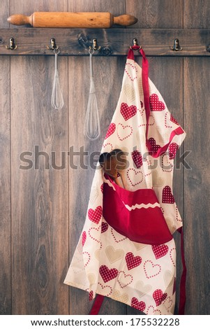 Apron hanging on hook in kitchen with utensils - vintage tone effect - stock photo