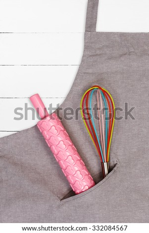 Apron with pink rolling pin and whisk on white wooden background
