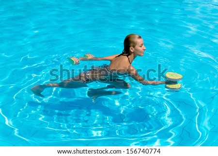 Aqua aerobic, woman in water with dumbbells - stock photo