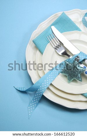 Aqua blue Merry Christmas dining table place setting with fine china and polka dot cutlery on blue background with copy space.