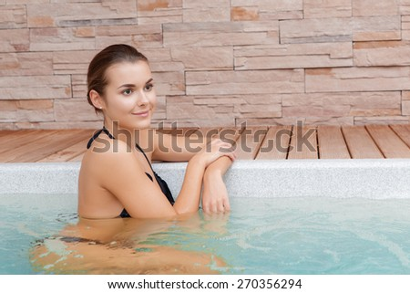 Aqua therapy. Young smiling woman leaning upon the edge of a Jacuzzi  - stock photo