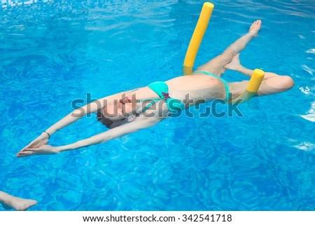 Aqua Yoga; a pregnant woman does her yoga exercises at the pool - stock photo