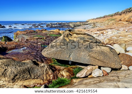Aquamarine sea & blue sky, green algae pools, rock, & unusual geological formations at low tide, along the rugged Big Sur coastline (Highway 1), near Cambria, CA. on the California Central Coast. - stock photo