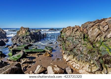 Aquamarine sea & blue sky, green algae pools, rock, & unusual geological formations at low tide, along the rugged Big Sur coastline (Highway 1), near Monterey, CA. on the California Central Coast. - stock photo