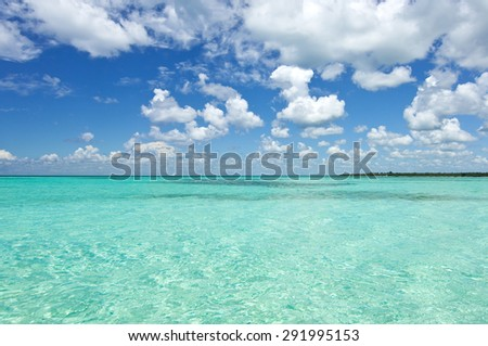 Aquamarine water and sky with clouds