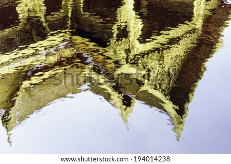 Aquatic abstract: Reflection of gilded pavilion in slightly rippled pool - stock photo