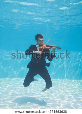 Aquatic music underwater violinist in suit - stock photo