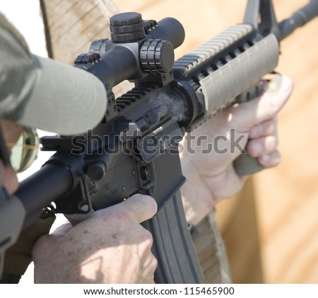 AR-15 with smoke coming from its chamber as another round is chambered - stock photo