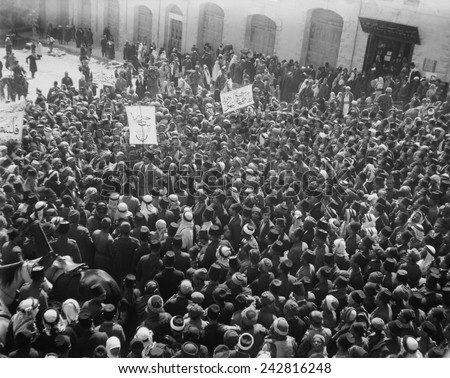 Arab Anti-Zionist demonstration is outside the Damascus Gate in Jerusalem. Jewish people are watching demonstration near door. March 8, 1920. - stock photo