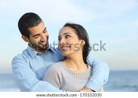 Arab casual couple cuddling happy with love on the beach with the horizon and the sea in the background                - stock photo