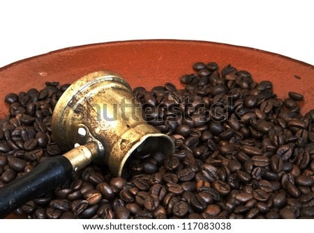 Arab coffee pot and roasted coffee beans on old ceramic plate over white background - stock photo