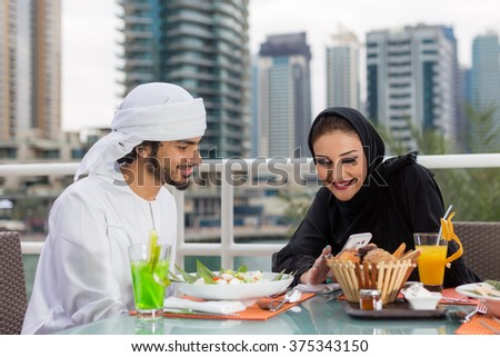 Arab couple dining at a restaurant - stock photo