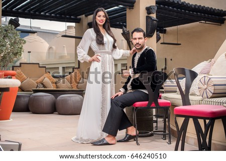 Arab couple standing and looking in the camera. Couple dressed in traditional Middle Eastern closes. Ramadan Holiday mood.