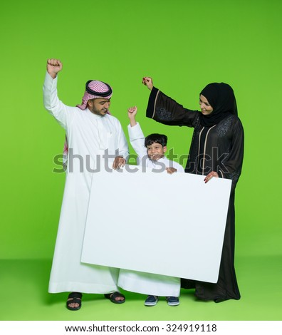 Arab family holding blank placard and cheering - stock photo
