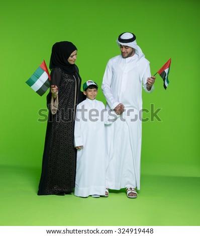 Arab family holding UAE national flag - stock photo