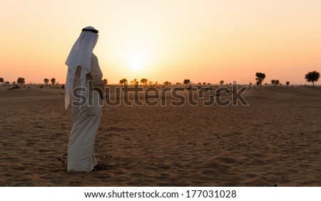 Arab man stands alone in the desert and watching the sunset  - stock photo