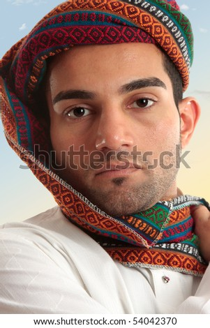 Arab man wearing a colourful wovan turban style  head piece.  These  serve a purpose of protecting nose and mouth from dust and sand storms as the fabric can be wrapped across the face when needed.
