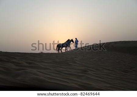 Arab Man with Arabian Horses in the desert during sunset - stock photo